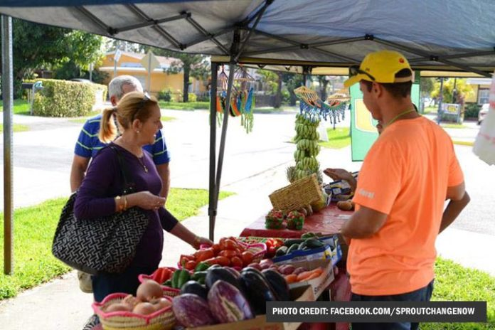 resident purchases produce at sweetwater community market